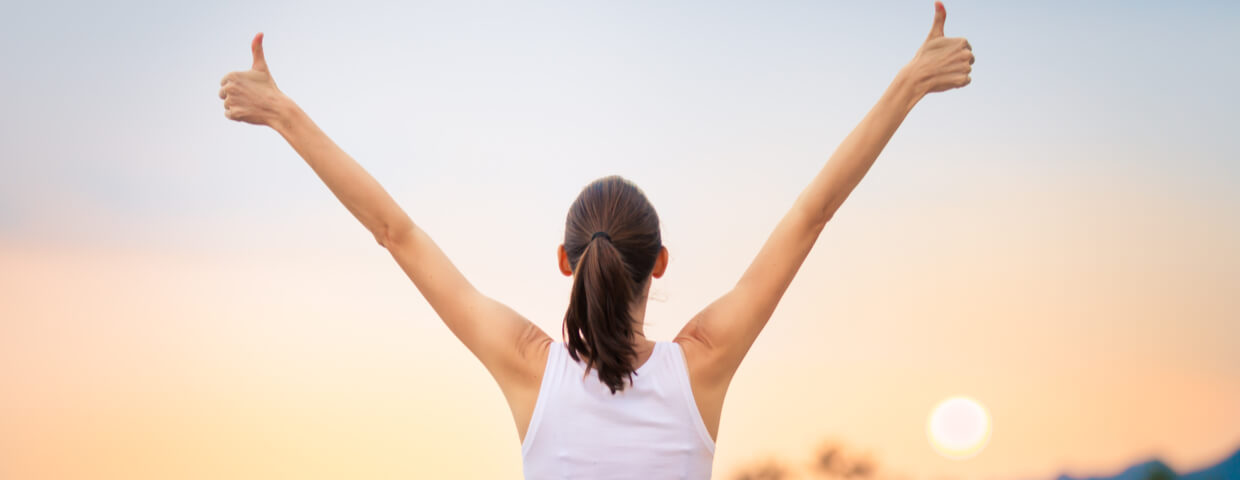 woman with arms raised in thumbs up facing a sunset