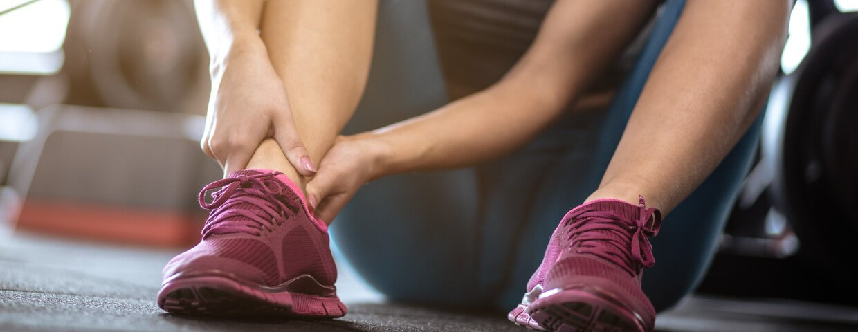 Woman having pain in ankle/leg after exercise. close up. focus is on leg.