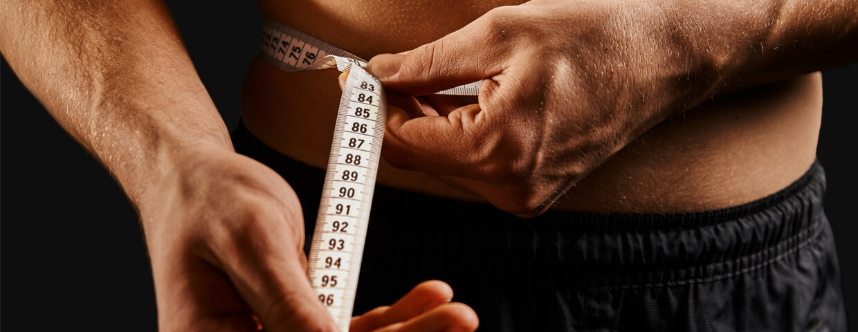 close up of a man measuring weight loss with tape