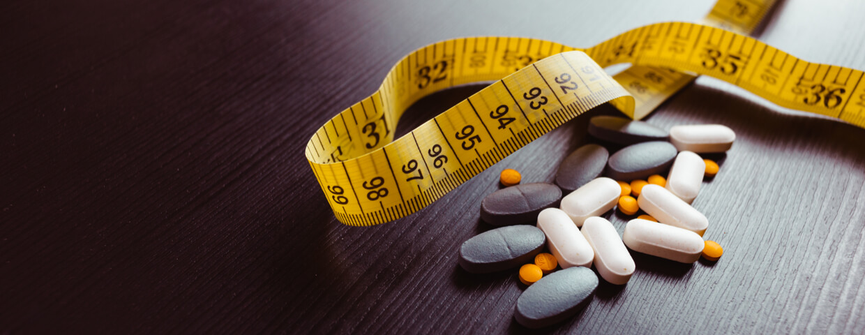 Many different weight loss pills, or appetite suppressants, and supplements, with measuring tape on black wooden table. Diet pills and supplements, prescription weight loss drugs.