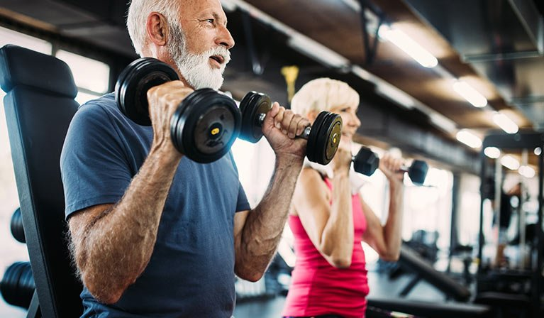 Elderly couple lifting weights in a gym