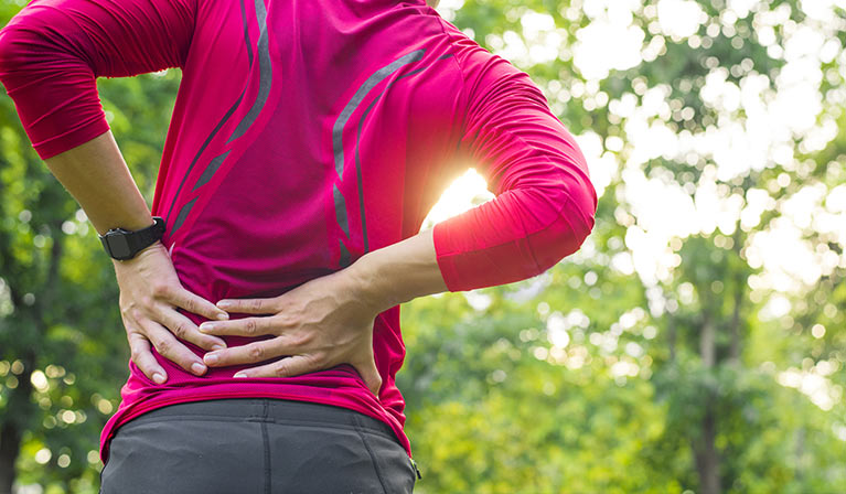 Jogger holding lower back in pain