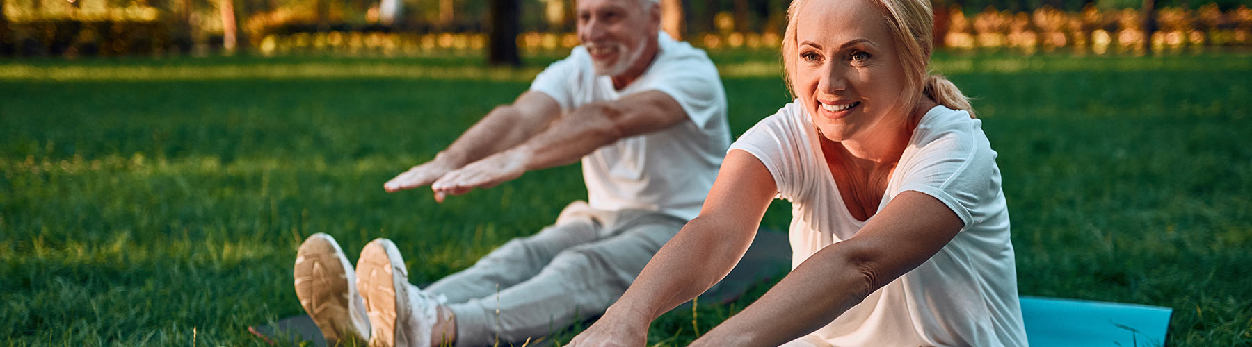 Middle aged couple stretching in park
